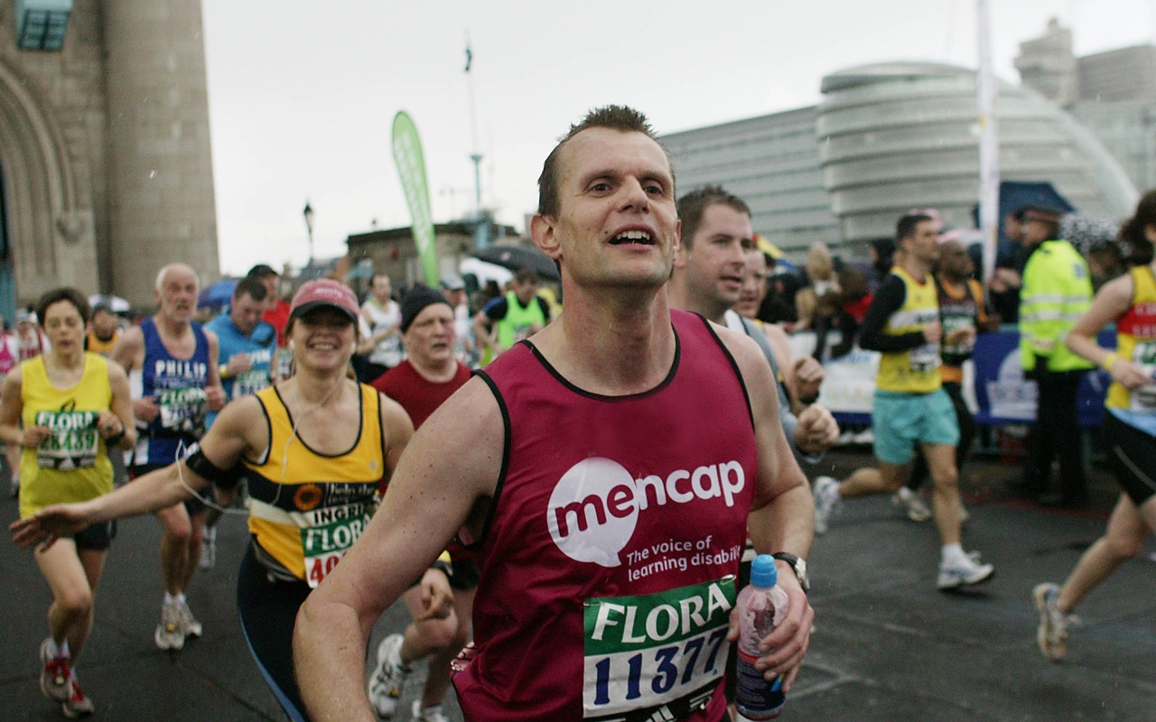 A man running in a Mencap sponsored shirt for charity